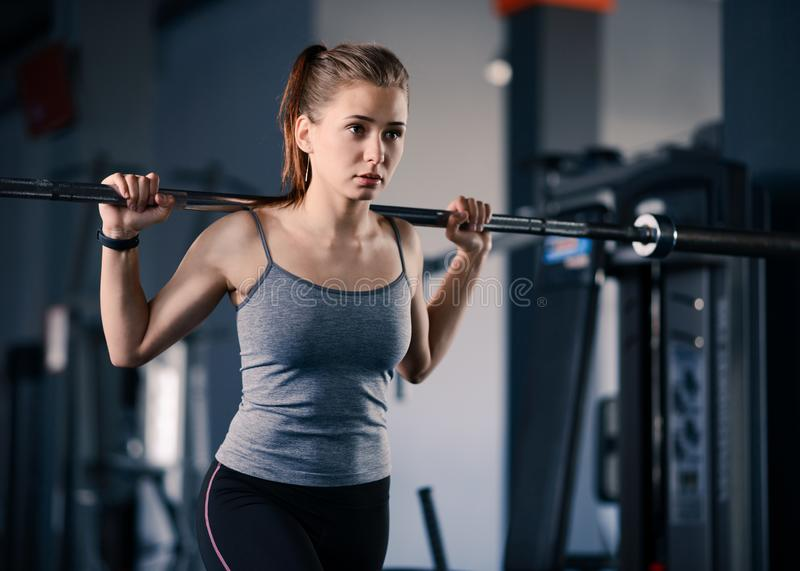 Attractive Young Sports Woman Doing Lunges with Barbell in the Gym. Fitness and Healthy Lifestyle. stock photo