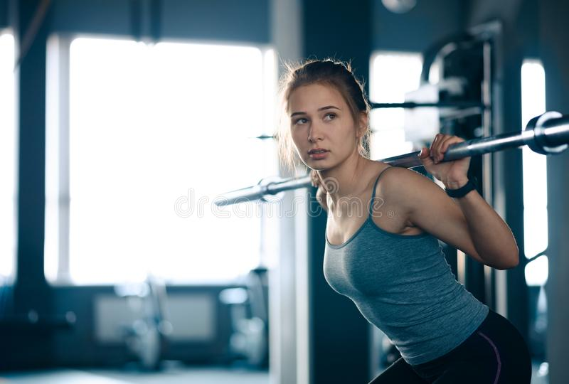 Attractive Young Sports Woman Doing Squats with Barbell in the Gym. Fitness and Healthy Lifestyle. stock images