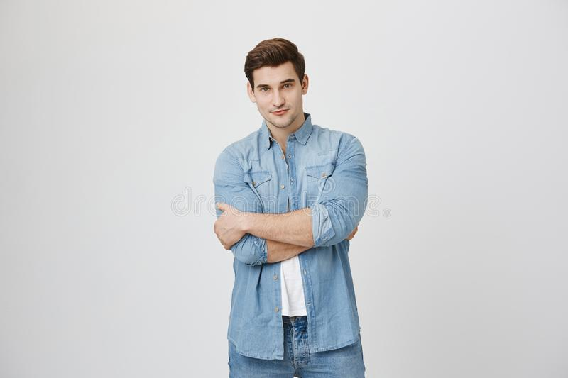 Attractive young sportsman with beautiful eyes, confident expression and crossed hands near white background. Artist royalty free stock photo