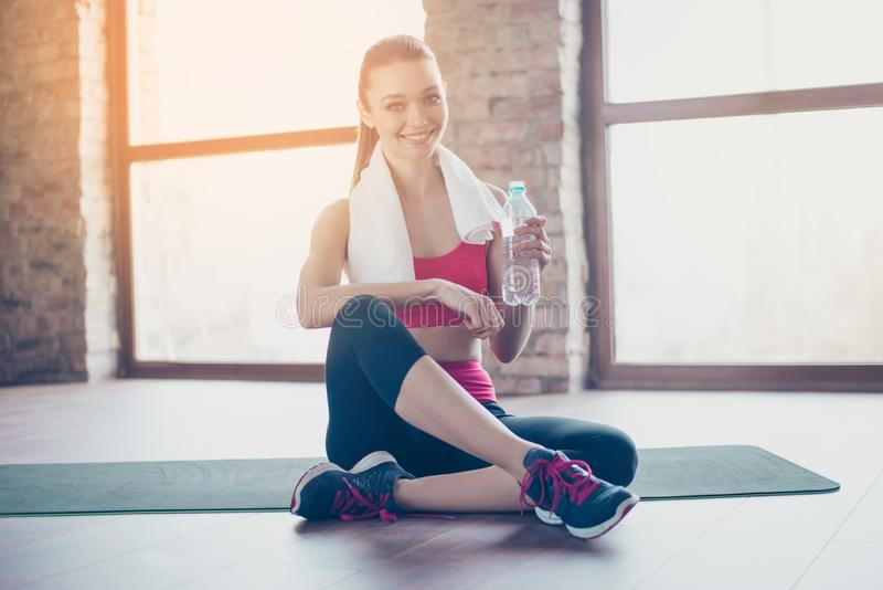 Attractive young sportwoman finished her work out and now drinking water and smiling. She is sitting on the floor in sunny room w stock images