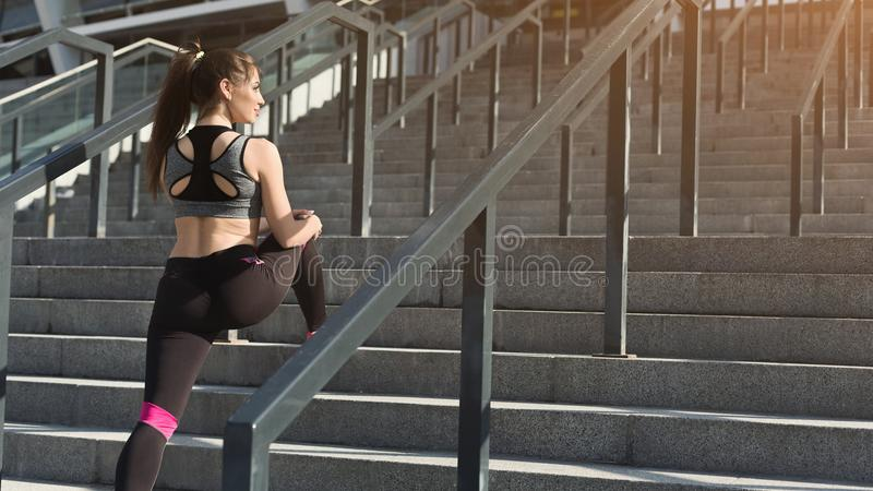 Attractive young sporty woman stretching on stairs stock photography