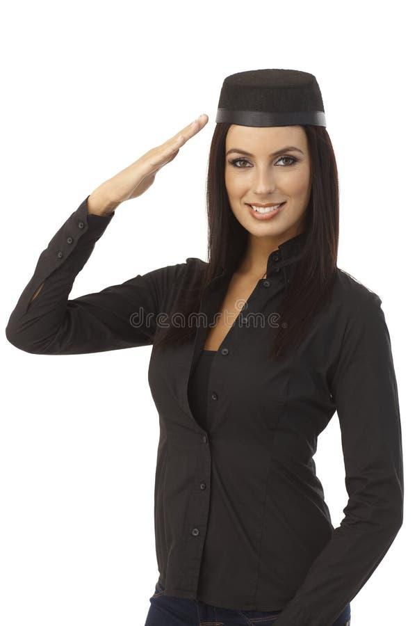 Happy cabin crew saluting. Attractive young stewardess saluting stock photos
