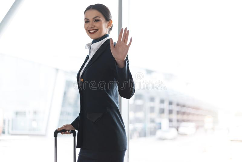attractive young stewardess with suitcase waving at camera royalty free stock image