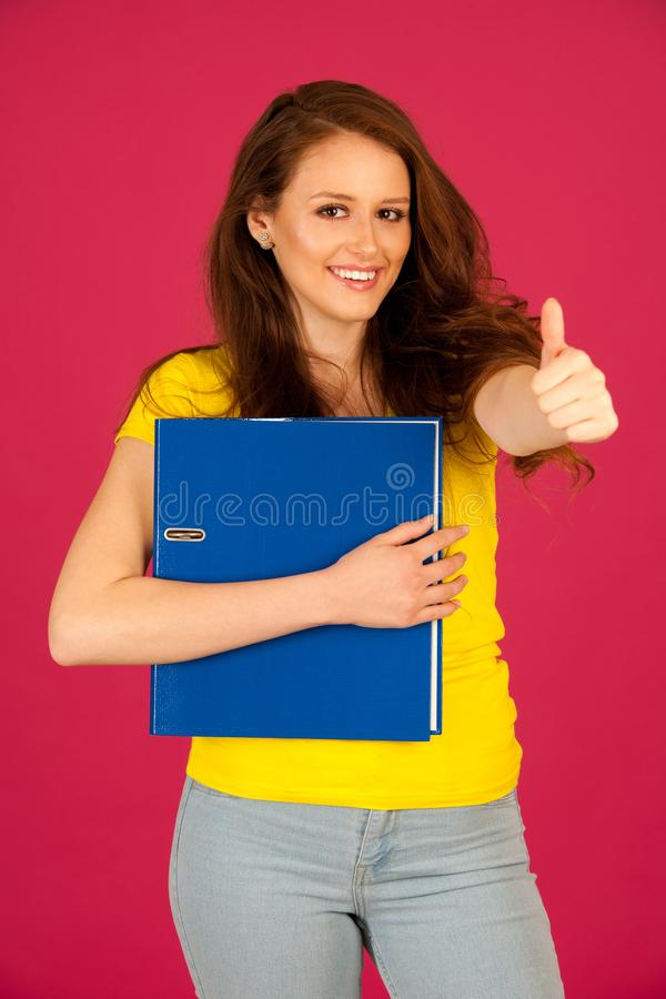 attractive young student in yellow t shirt holding red folder over pink background stock photos