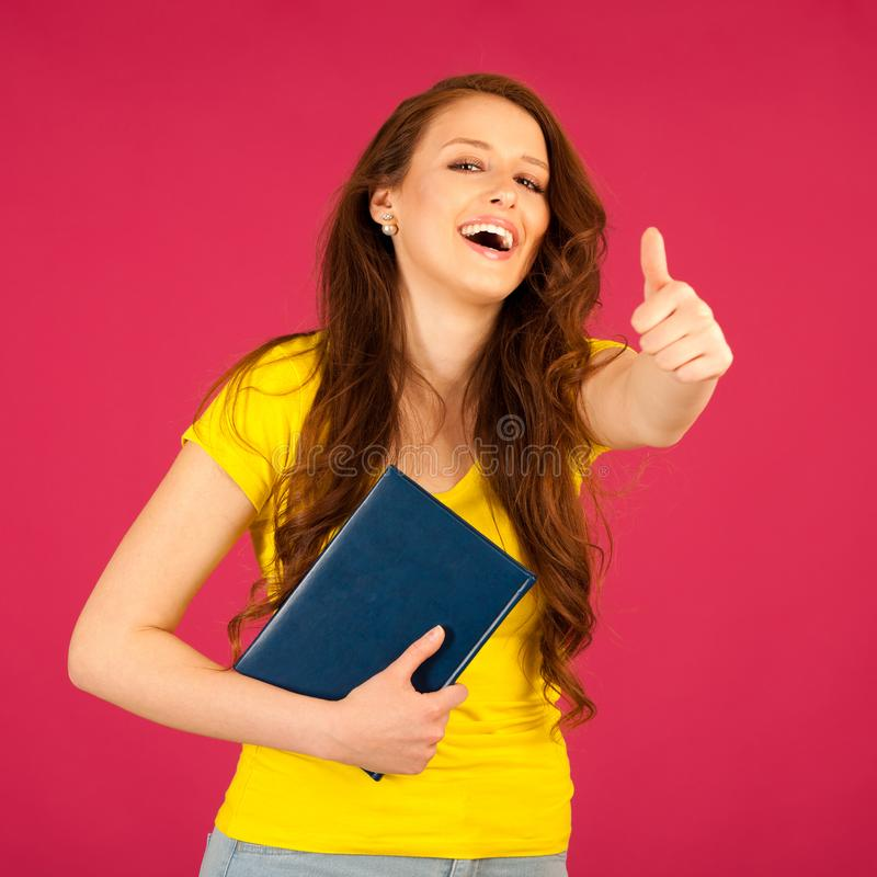 attractive young student in yellow t shirt holding red folder over pink background stock image
