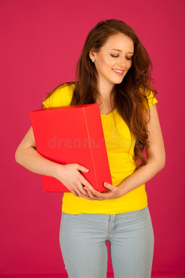 attractive young student in yellow t shirt holding red folder over pink background royalty free stock photography