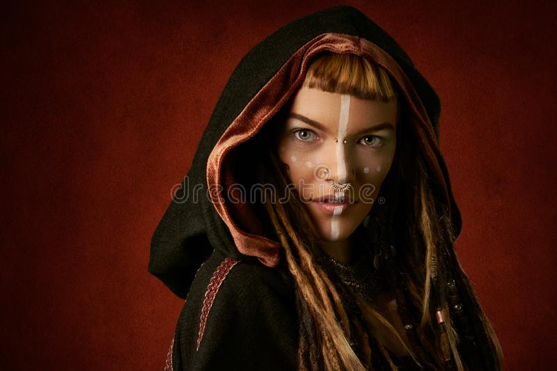 Attractive, young, stylish woman in a black, tribal hood on red background stock photo