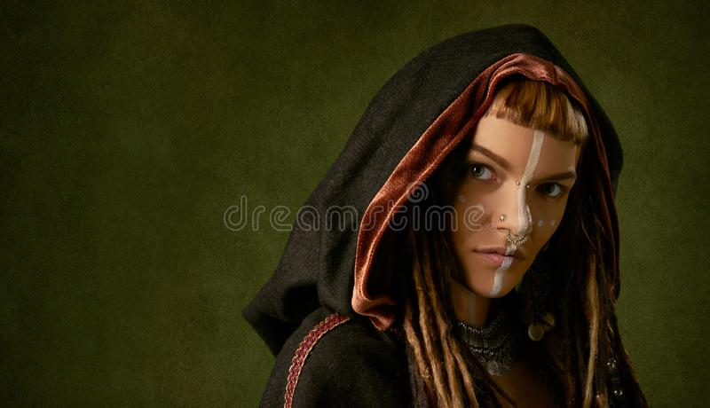 Beautiful, young, stylish woman in a black, tribal hood on green background royalty free stock image