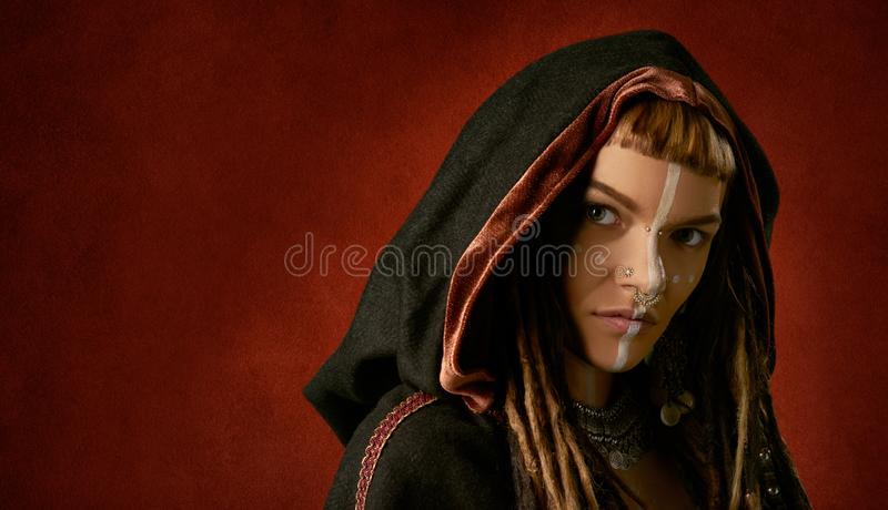 Beautiful, young, stylish woman in a black, tribal hood on red background royalty free stock photography