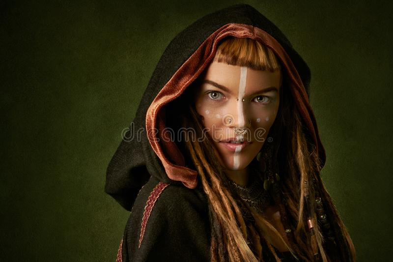 Attractive, young, stylish woman in a black, tribal hood on green background royalty free stock images