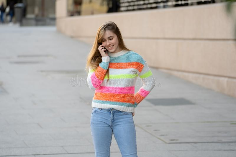 Attractive young teenager woman talking and chatting on her smart phone outside in an European city stock image