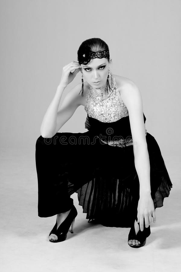 Attractive Young Woman in 1920s Dress. Attractive young woman squatting in a 1920s flapper style dress. Vertical shot royalty free stock images
