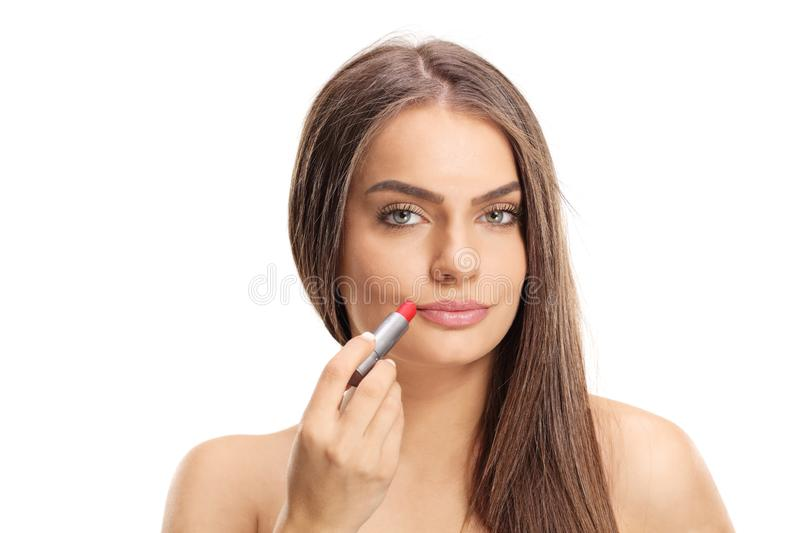 Attractive young woman applying red lipstick stock photography