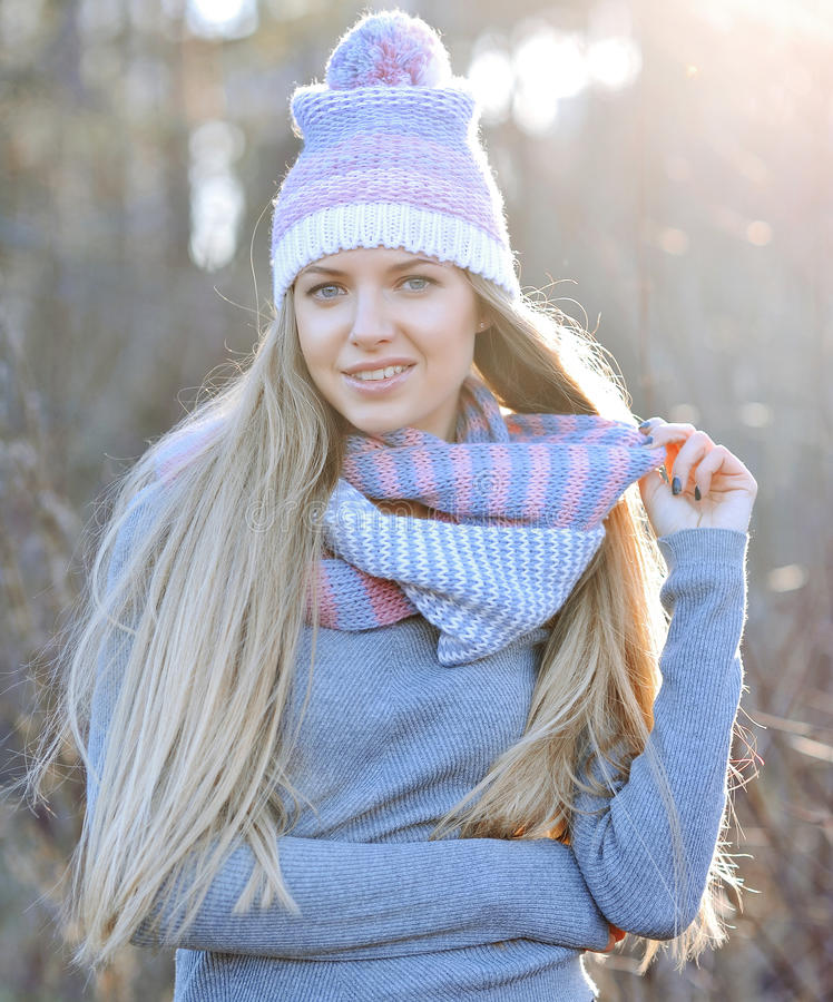 Attractive young woman in autumn fashion shot wearing cap, a grey woolen sweater and a purple scarf. Attractive young girl in autumn fashion shot wearing cap, a stock images