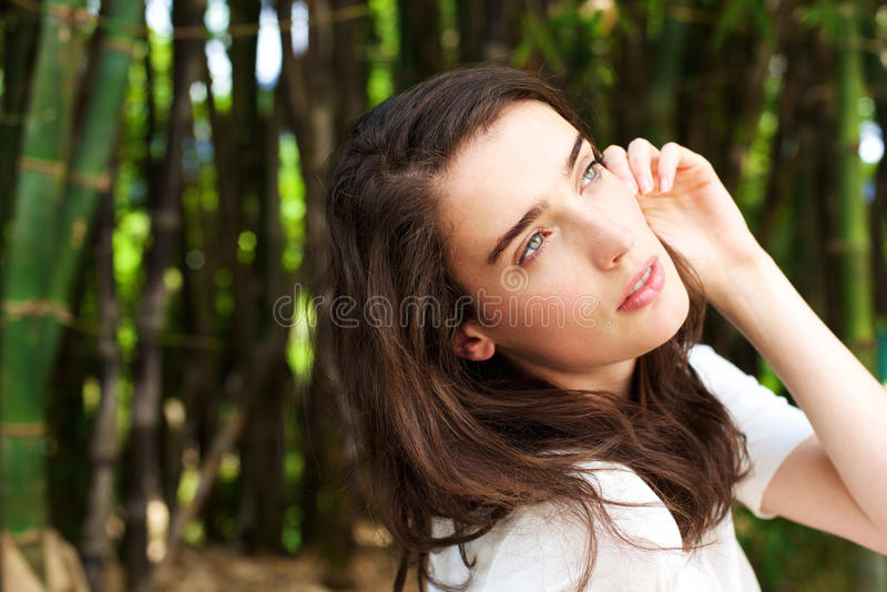 Attractive young woman by bamboo trees looking up royalty free stock images