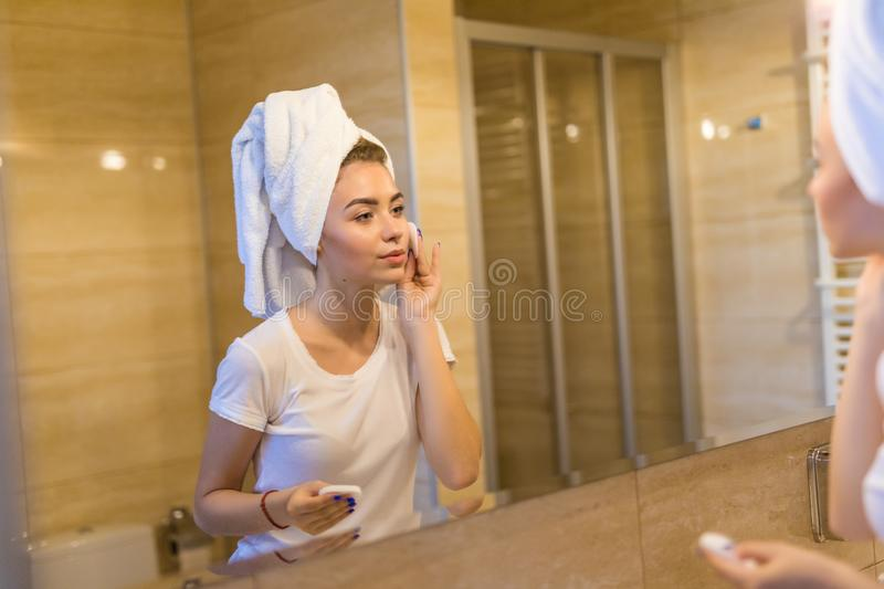 Attractive young woman in bathroom after shower is standing in front of mirror with face sponge. Women bodycare. Attractive young woman in bathroom after shower stock photo