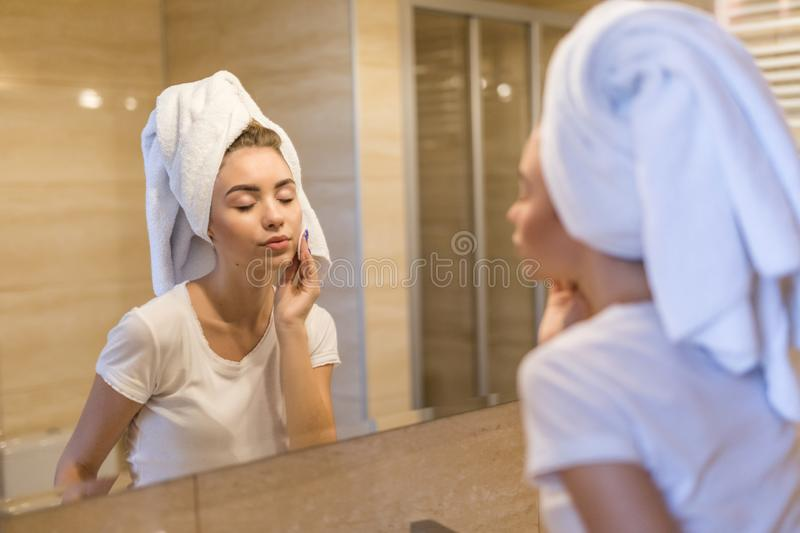 Attractive young woman in bathroom after shower is standing in front of mirror with face sponge. Women bodycare. Attractive young woman in bathroom after shower royalty free stock photo