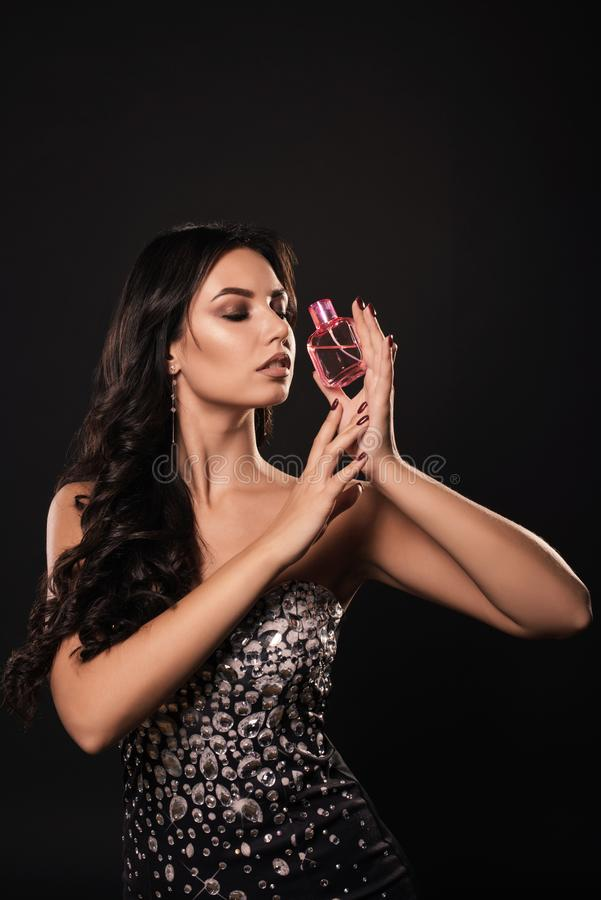 Attractive young woman in a beautiful dress with perfume on dark background royalty free stock image