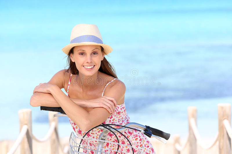 Attractive young woman on bicycle standing by the fence on the beach royalty free stock photo