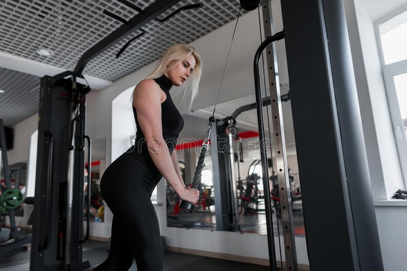 Attractive young woman blonde in sportswear doing strength exercises for hands with the help of modern simulator royalty free stock photography