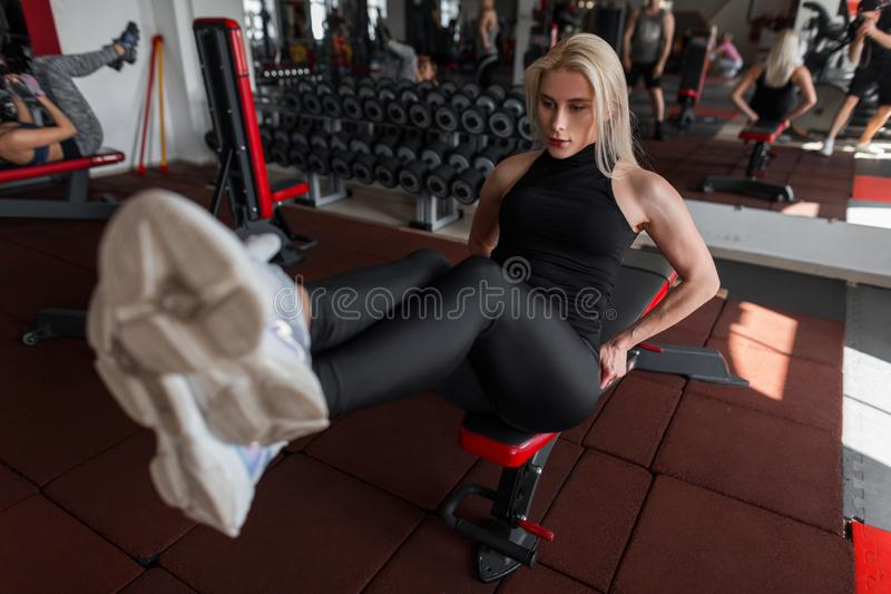 Attractive young woman blonde trains sitting in the gym. Girl does exercises for the abdominal muscles royalty free stock photo