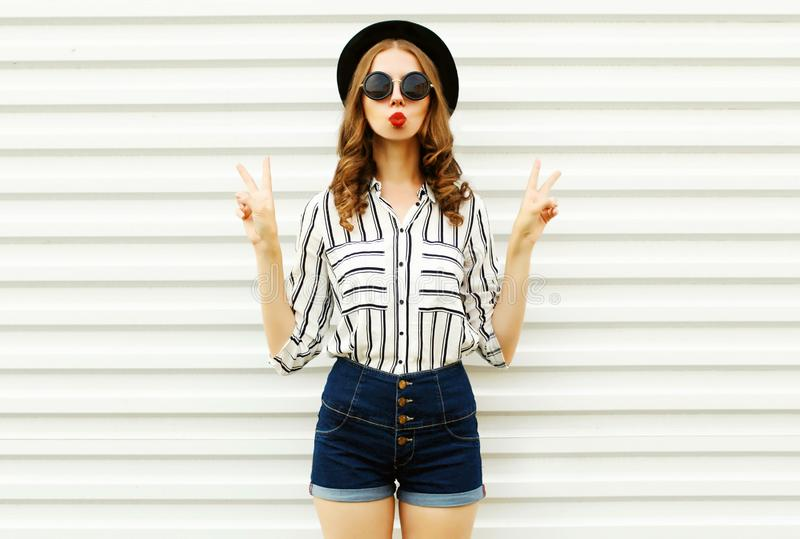 Attractive young woman blowing red lips sending sweet air kiss in black round hat, shorts, white striped shirt on white wall. Background royalty free stock images