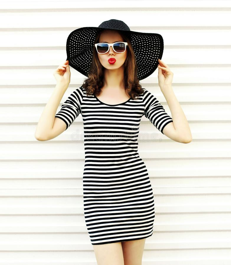 Attractive young woman blowing red lips sending sweet air kiss in black summer straw hat on white wall royalty free stock images