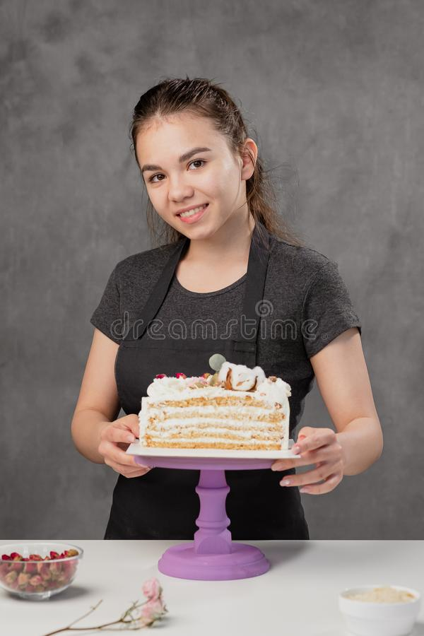 Attractive young woman brunette confectioner presents a white cake with small red flowers of a food rose. stock images