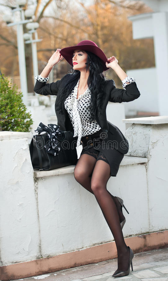 Attractive young woman with burgundy colored large hat in autumnal fashion shot. Beautiful lady in black outfit with short skirt stock photography