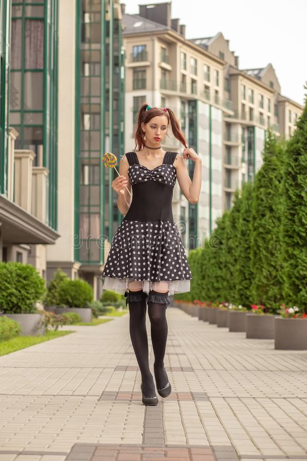Pretty beautiful girl. Attractive young woman with candy in black dress walking on street royalty free stock photos