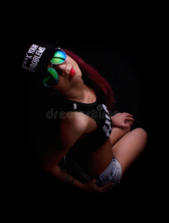 Attractive young woman in cap and sunglasses, smokes on a dark background. Be trendy, be rapper.  royalty free stock image