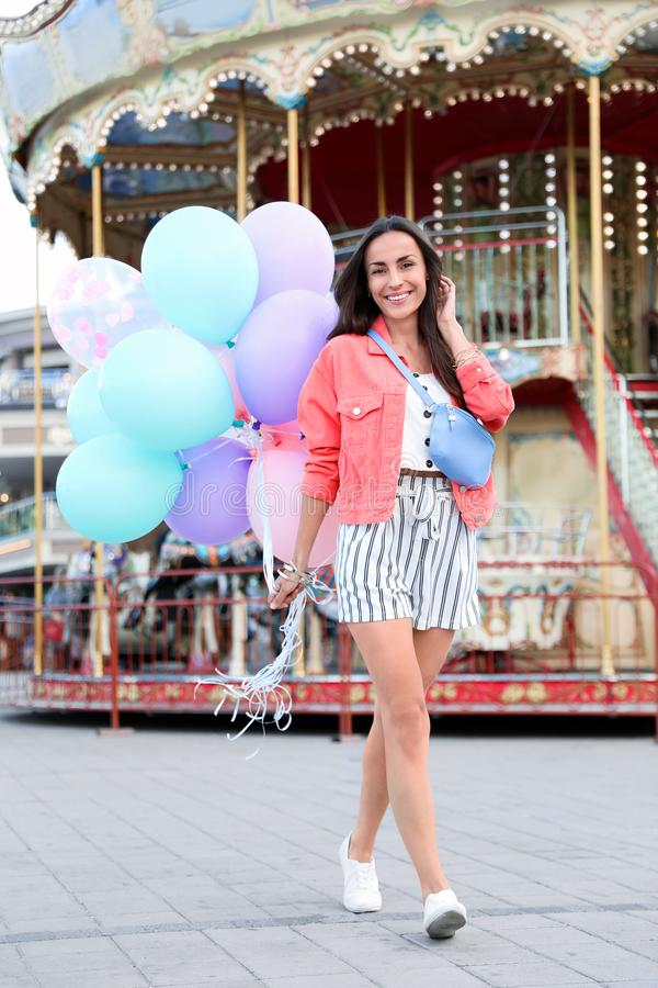 Attractive young woman with color balloons. Near carousel stock photos