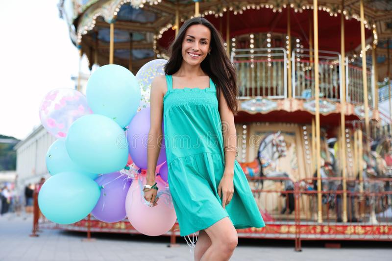 Attractive young woman with color balloons. Near carousel royalty free stock images