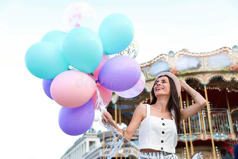 Attractive young woman with color balloons. Near carousel royalty free stock photos