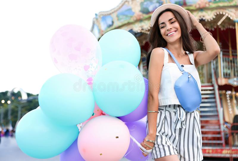 Attractive young woman with color balloons. Near carousel stock images