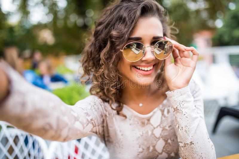 Attractive young latin woman in sunglasses with curly hair takes a selfie, posing and looking at camera, outdoors. stock photos