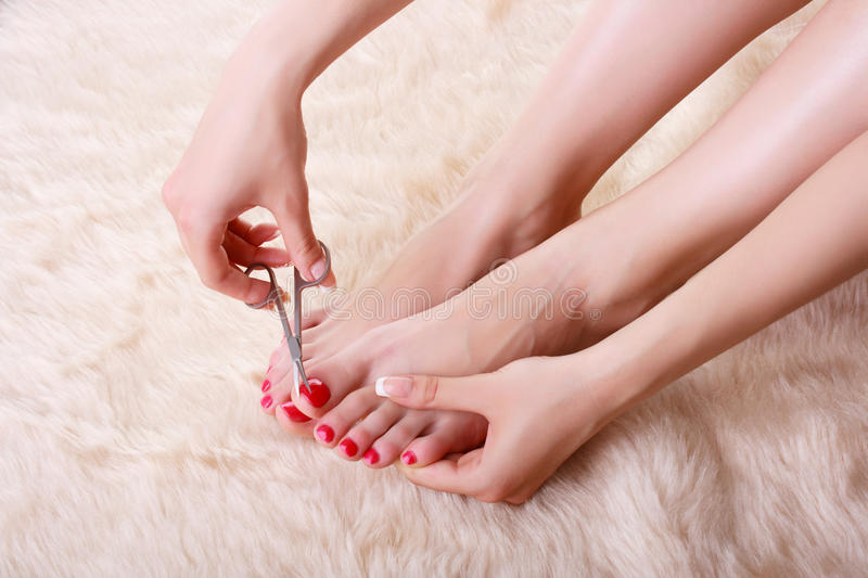 Attractive young woman cutting her feet nails stock images