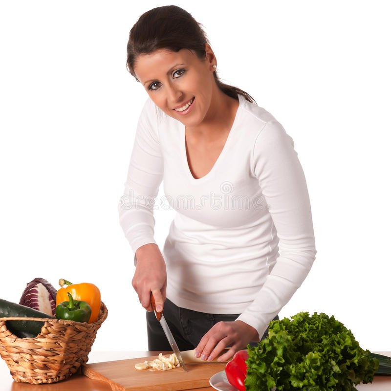 Attractive young woman cutting vegetables stock image