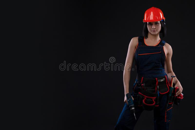 Attractive young woman doing repairs at black background. Portrait of a female construction worker. Building, repair concept. Copy royalty free stock images