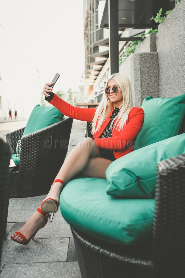 Attractive young woman is doing selfie in a street cafe stock photos