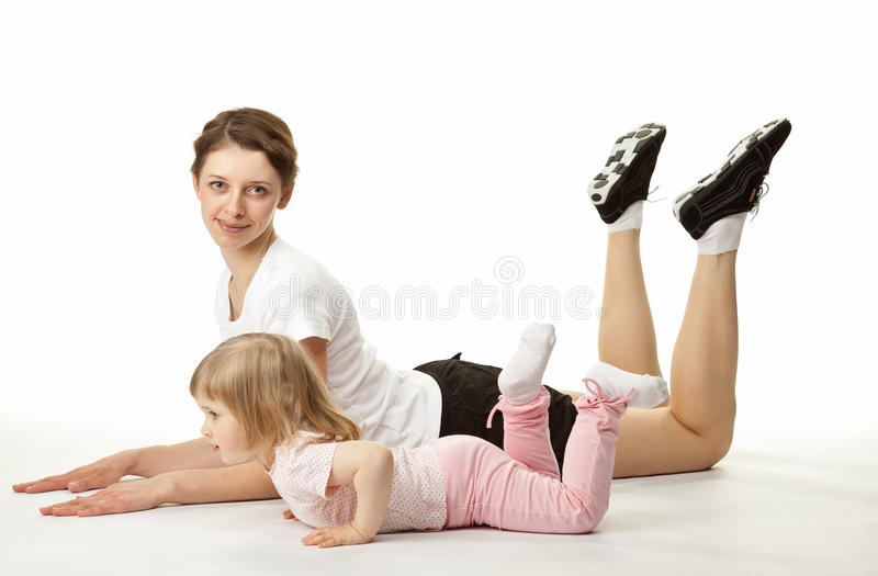 Attractive young woman doing sport exercises with her little daughter royalty free stock images