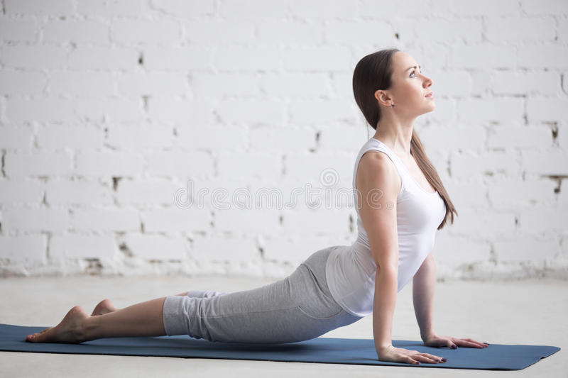 Attractive young woman doing upward facing dog pose in white loft stock image