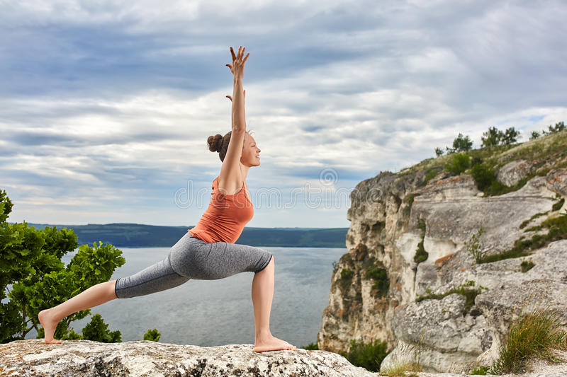 An attractive young woman doing a yoga pose for balance on the rock. royalty free stock images