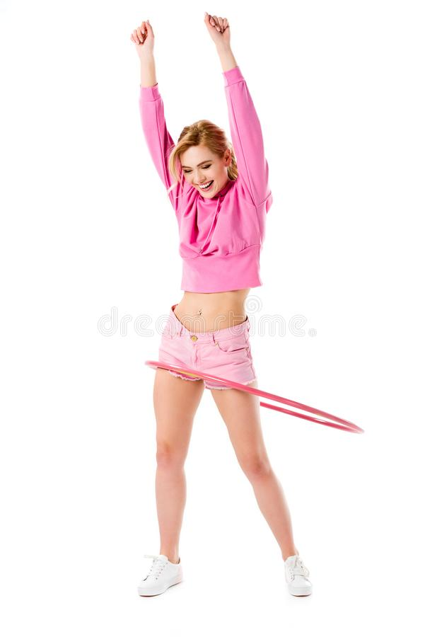 Attractive young woman dressed in pink exercising with hula hoop royalty free stock photo