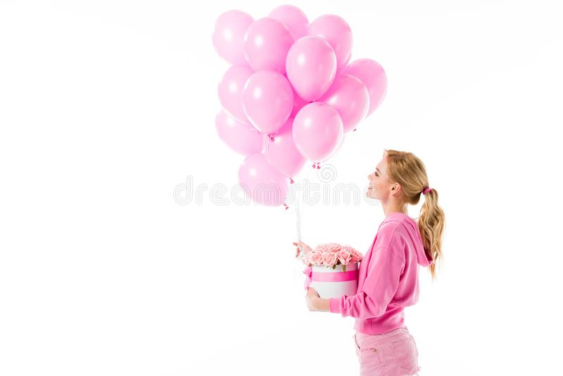 Attractive young woman dressed in pink holding balloons with flowers royalty free stock images