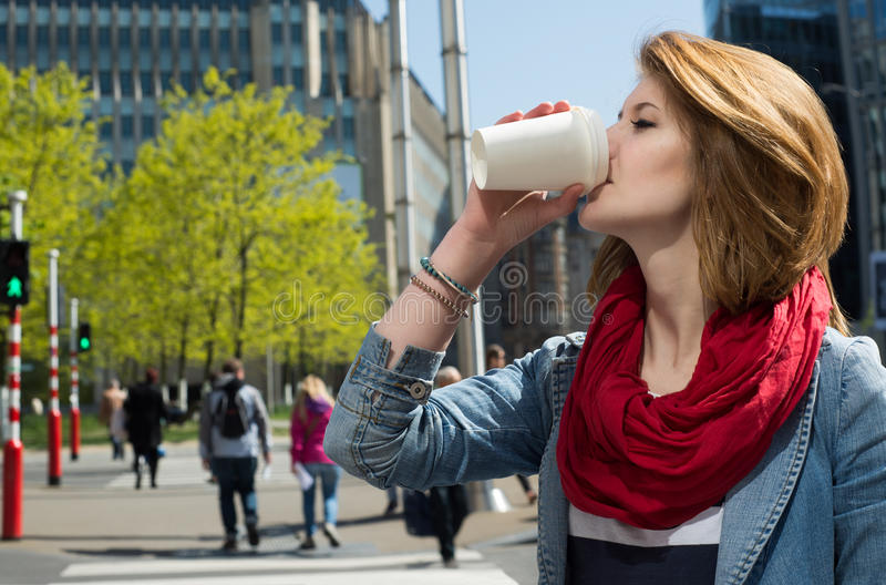 Attractive young woman drinking a hot drink from a paper cup. Attractive young woman enjoying a hot drink in a white paper cup against cityscape background stock photo