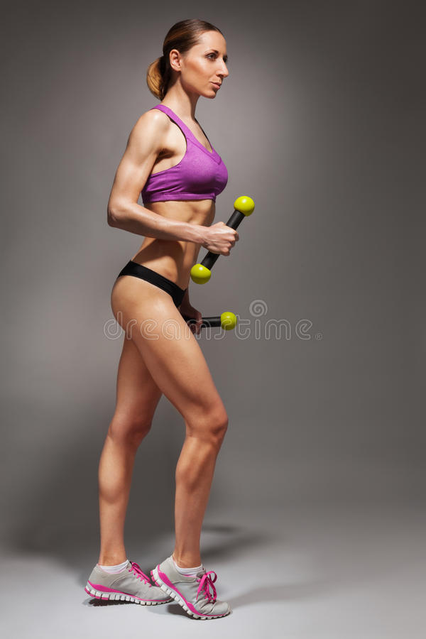 Attractive young woman with dumbbells. Full height side portrait view of healthy young fit woman with fitness dumbbells on dark background stock photos