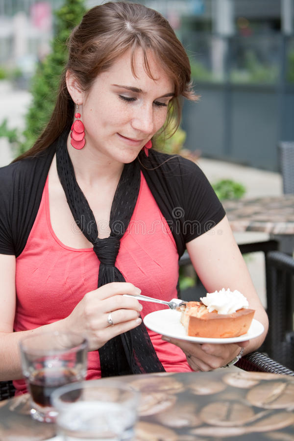Attractive young woman eating apple pie royalty free stock image