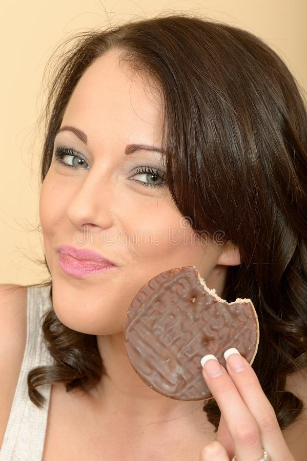 Attractive Young Woman Eating a Milk Chocolate Covered Rice Cake royalty free stock photography