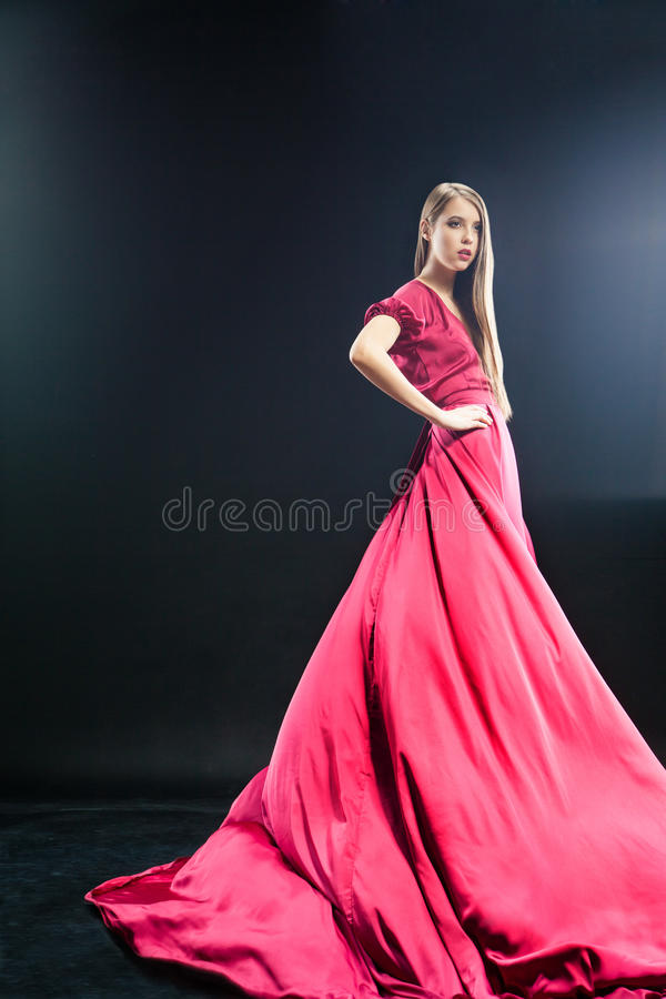 Attractive young woman in elegant long pink dress stock images